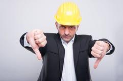 El casco de protección que lleva del capataz que hace el pulgar abajo gesticula Fotos de archivo