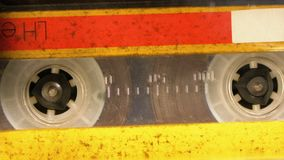 El casete audio amarillo en la grabadora que juega y gira metrajes