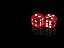 El casino de dos rojos corta en cuadritos con la reflexión Fondo negro Imágenes de archivo libres de regalías