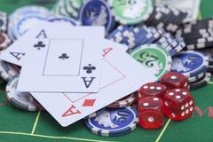 El casino salta, las tarjetas y corta en cuadritos en la mesa de juegos del fieltro del verde Imágenes de archivo libres de regalías