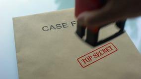 El caso archiva de alto secreto, mano que sella el sello en carpeta con los documentos importantes almacen de metraje de vídeo