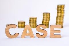 El caso de la palabra de letras tridimensionales está en primero plano con las columnas del crecimiento de monedas en fondo borro Imagen de archivo libre de regalías