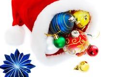 El casquillo de Papá Noel con las esferas aisladas en el fondo blanco Fotografía de archivo