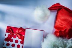 El casquillo de Papá Noel envolvió la actual caja en el fondo blanco foto de archivo