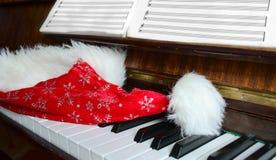 El casquillo de Papá Noel miente en un piano Foto de archivo