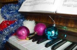 El casquillo de Papá Noel y las decoraciones de la Navidad mienten en un piano Imagen de archivo