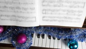 El casquillo de Papá Noel y las decoraciones de la Navidad mienten en un piano Fotografía de archivo libre de regalías