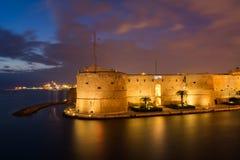 El castillo de Aragonian en el mar del barco de canal de Taranto ilumina Imagen de archivo libre de regalías