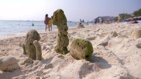 El castillo en la playa, coral de la arena expulsado por el mar para apuntalar, una familia irreconocible camina en una playa p?b metrajes