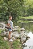 El caucásico bronceó soportes envejecidos centro de la mujer delante del lago Fotografía de archivo libre de regalías