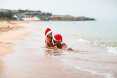 El caucásico bronceado embroma a hermanas en los sombreros de santa en la playa con yello Fotos de archivo