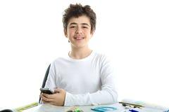 El caucásico liso-peló sonrisas del muchacho usando smartphone en la preparación Foto de archivo libre de regalías