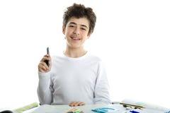El caucásico liso-peló sonrisas del muchacho usando smartphone en la preparación Fotos de archivo libres de regalías