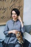 El caucásico que la mujer embarazada con compone en vestido gris abraza su vientre con el búho que se sienta en su brazo, retrato fotos de archivo libres de regalías