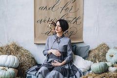 El caucásico que la mujer embarazada con compone en vestido gris abraza su vientre con el búho que se sienta en su brazo, retrato fotos de archivo