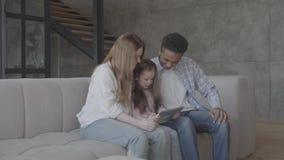 El caucásico rubio caucásico joven de la mujer del retrato se sienta con el hombre negro africano y entre ellos es pequeña hija a almacen de video