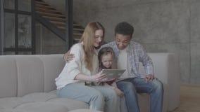 El caucásico rubio caucásico joven de la mujer se sienta con el hombre negro africano y entre ellos es pequeña hija adorable almacen de metraje de vídeo