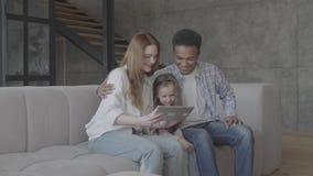 El caucásico rubio joven de la mujer se sienta con el hombre negro africano y entre ellos es pequeña hija adorable Familia intern almacen de video