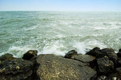 El causar un crash agita contra rocas en línea de la playa. Imágenes de archivo libres de regalías