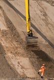 El cavador funciona en el nuevo sitio de la construcción de carreteras Foto de archivo libre de regalías