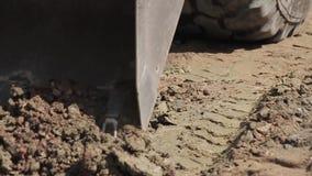 El cavador traspala la arena, obras por carretera almacen de video