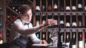 El cavist masculino examina las botellas con el vino y las notas de la fabricación en su libreta almacen de metraje de vídeo