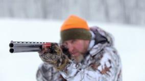 El cazador con el rifle de dos cañones El cazador en blancos del camuflaje con un rifle almacen de video