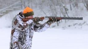 El cazador con el rifle de dos cañones El cazador en blancos del camuflaje con un rifle A cámara lenta almacen de metraje de vídeo