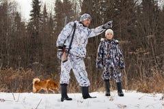 El cazador con su hijo en bosque del invierno Imágenes de archivo libres de regalías
