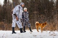 El cazador con su hijo y su perro en la caza del invierno Foto de archivo libre de regalías