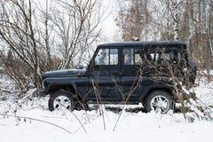 El CAZADOR de UAZ, auto ruso militar legendario parqueó en el bosque del invierno Imagenes de archivo