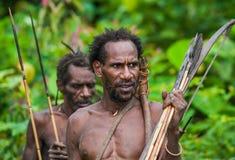El cazador del hombre de Korowai del retrato con la flecha y el arco Tribu de Korowai Kombai, Kolufo fotografía de archivo