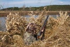 El cazador del pato se sienta en refugio durante la caza imagen de archivo