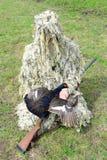 El cazador en camuflaje con un arma lleva a cabo urogallo foto de archivo