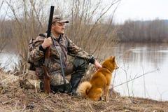 El cazador en la orilla foto de archivo