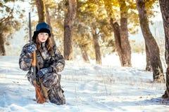 El cazador femenino en camuflaje viste listo para cazar, sosteniendo el arma a foto de archivo