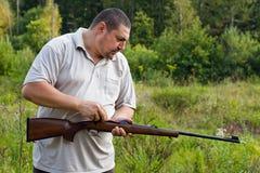 El cazador limpia el rifle Fotos de archivo libres de regalías