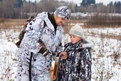 El cazador muestra a su hijo cómo cargar el arma Imagen de archivo libre de regalías