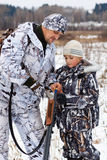El cazador muestra a su hijo cómo cargar el arma que se divierte Fotografía de archivo