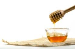 el cazo de la miel y la miel fragante en un aislador transparente del cuenco Foto de archivo