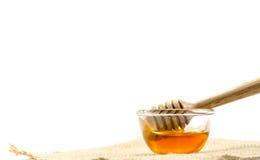 el cazo de la miel y la miel fragante en un aislador transparente del cuenco Imagen de archivo