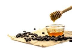 el cazo de la miel y la miel fragante en un cuenco transparente con Foto de archivo