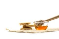 el cazo de la miel y la miel fragante en un cuenco transparente con Fotos de archivo libres de regalías