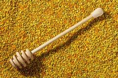 El cazo de madera de la miel en los gránulos del polen de la abeja emerge Foto de archivo