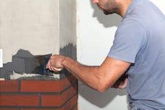 El cemento del hombre se aplica con una paleta Foto de archivo libre de regalías