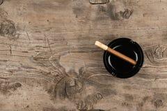 El cenicero de cristal con el cigarro se coloca en una superficie de madera Fotografía de archivo