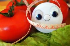 El centímetro de la salud con los ojos mira en el tomate y la ensalada Imagen de archivo libre de regalías