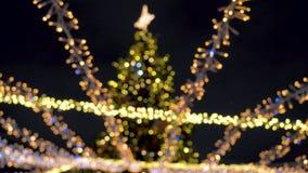 El centelleo borroso enciende a Garland On un árbol de navidad adornado en el cuadrado almacen de metraje de vídeo