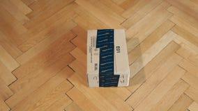 El centrarse al paquete de la caja de cartón del Amazonas en piso de madera del entarimado almacen de metraje de vídeo