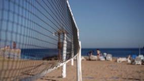 El centrarse en la red del voleibol en la cámara lenta en la playa del mar metrajes